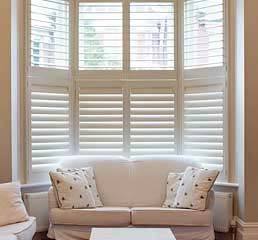 Image of a White Bay Window Plantation Shutter in a Living room by Perfect Shutters