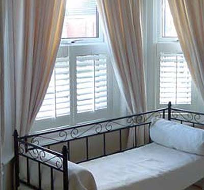 Image of a Plantation Shutters that Energy Efficient besides a day bed