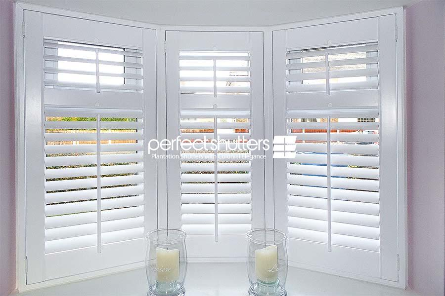 Open bay window shutters and two candles