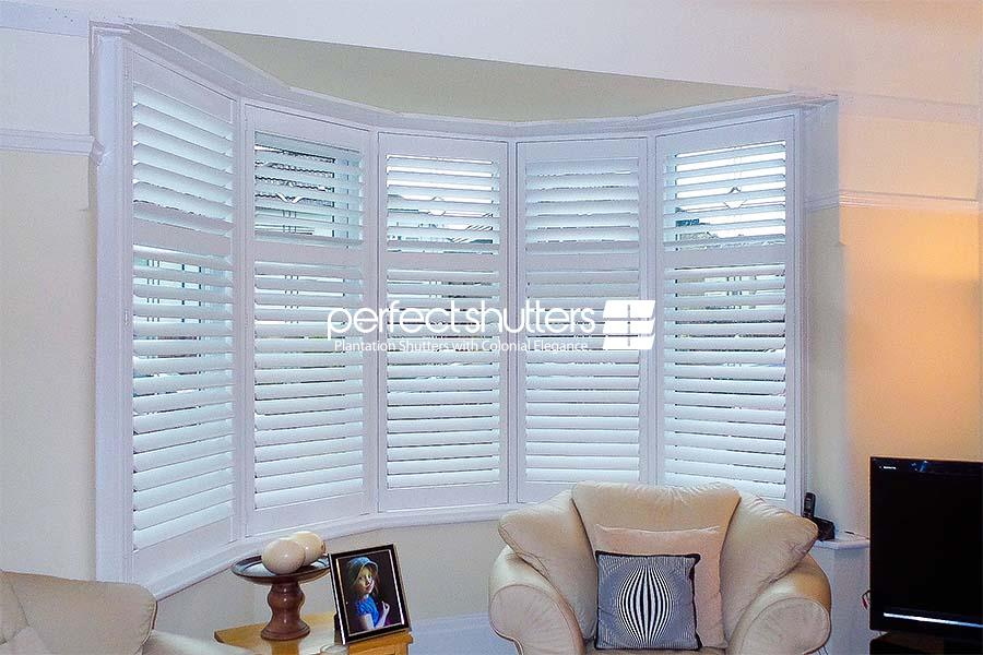 White bay window shutters in living room at dusk