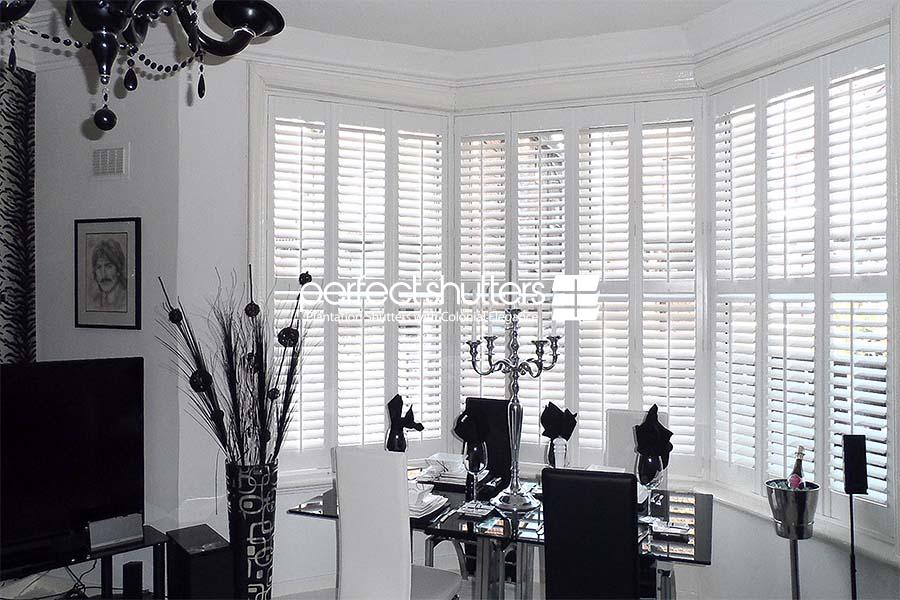 Bay window shutters - black and white dining area