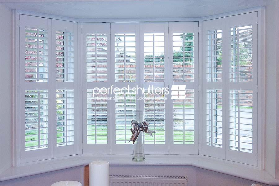 Open bay window shutters with view of driveway