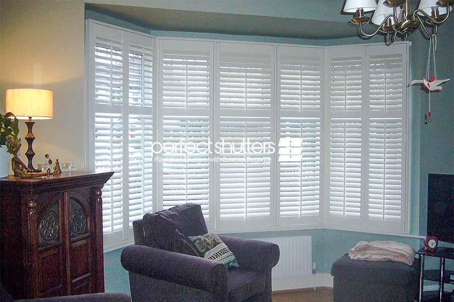 White bay window shutters in living room