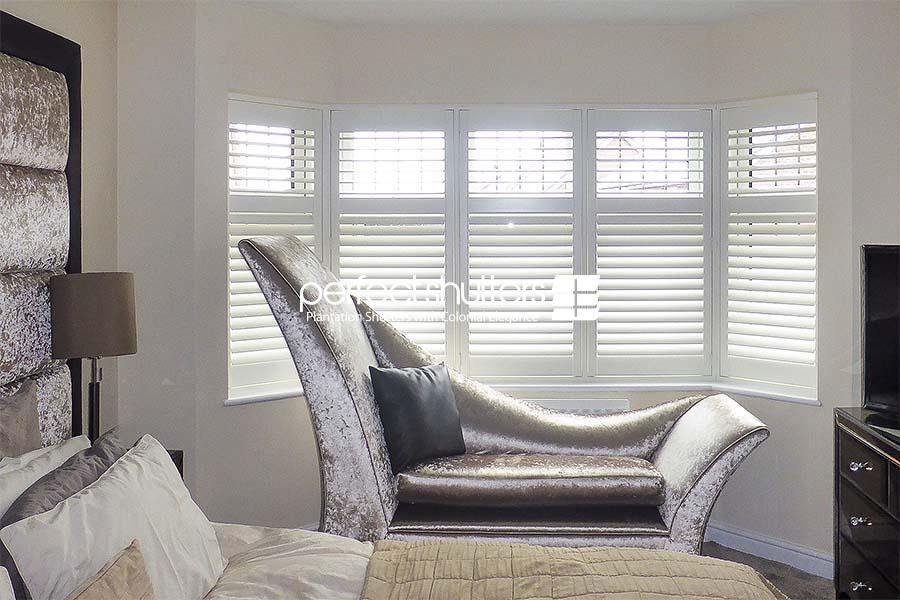 White bay window shutters in bedroom