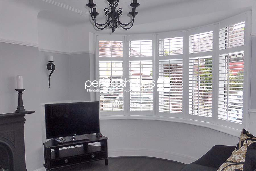 Bay window shutters open in living room