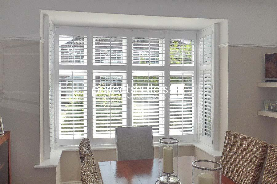Stylish bay window shutters in dining room