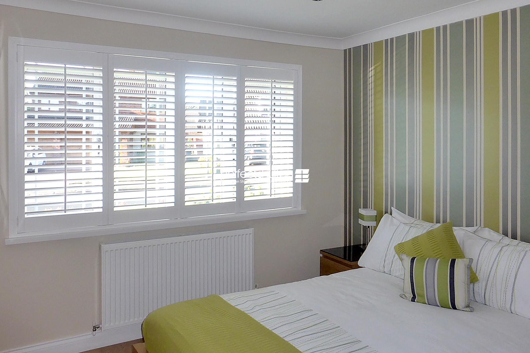 Shutter blinds in green bedroom