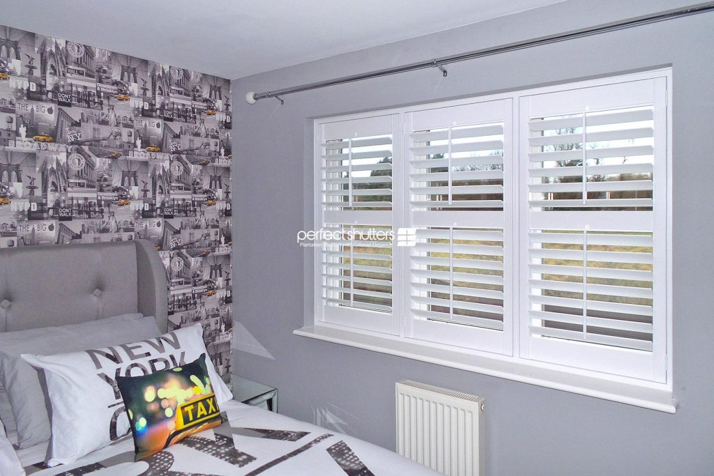 Open plantation shutters in New York themed bedroom