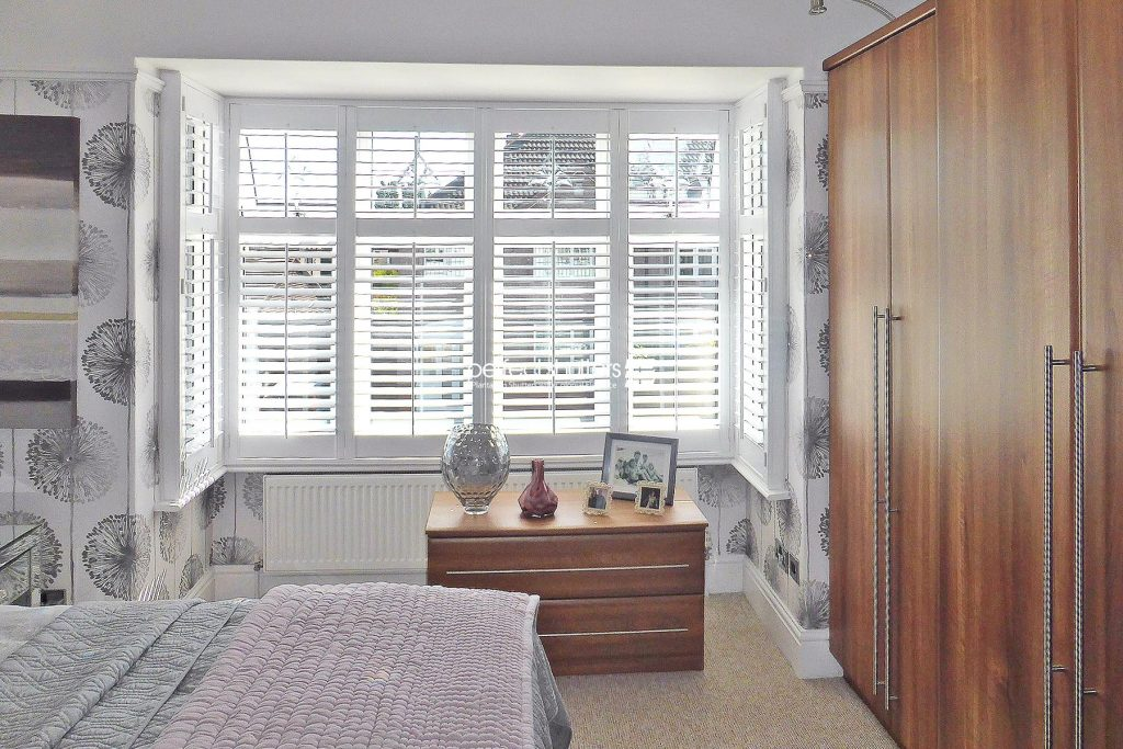 Plantation shutters in large bedroom