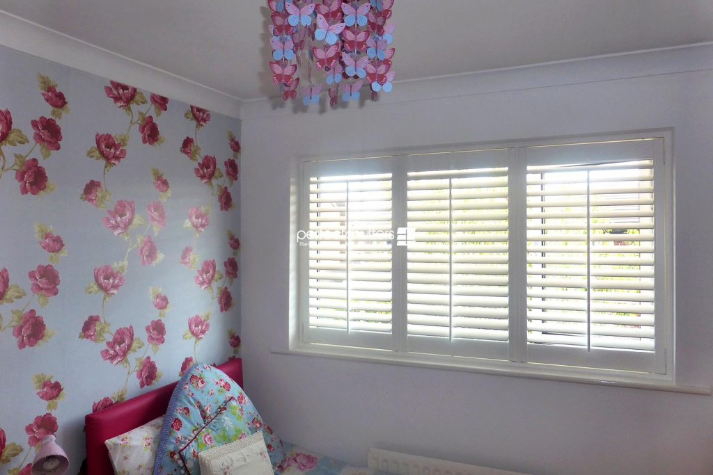 Wooden shutters in floral themed bedroom