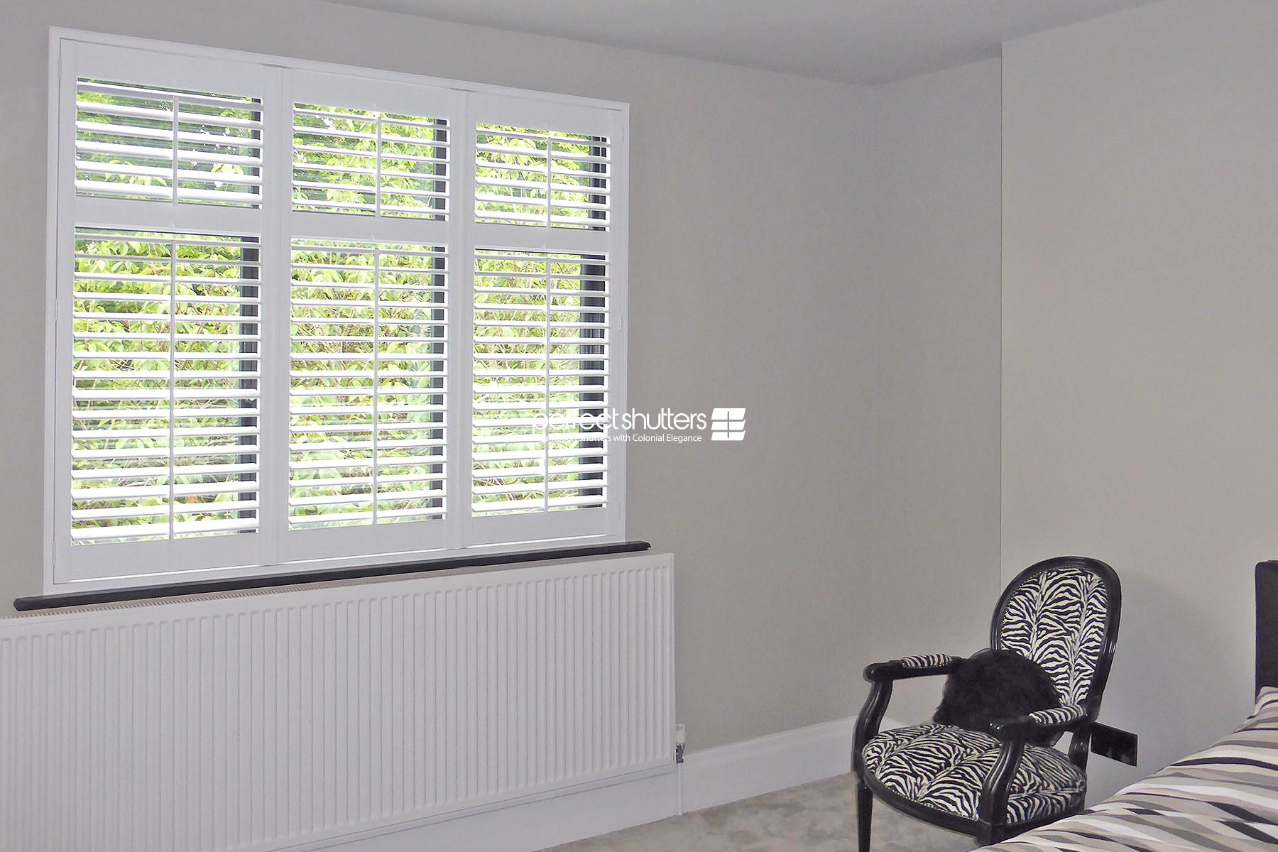 White plantation shutters in large bedroom
