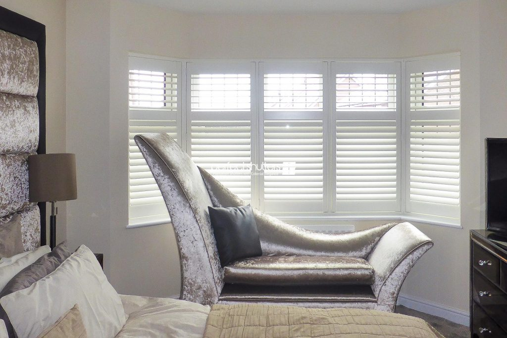 White wooden bay window shutters in bedroom