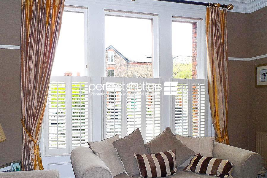 Cafe style shutters in living room with curtains
