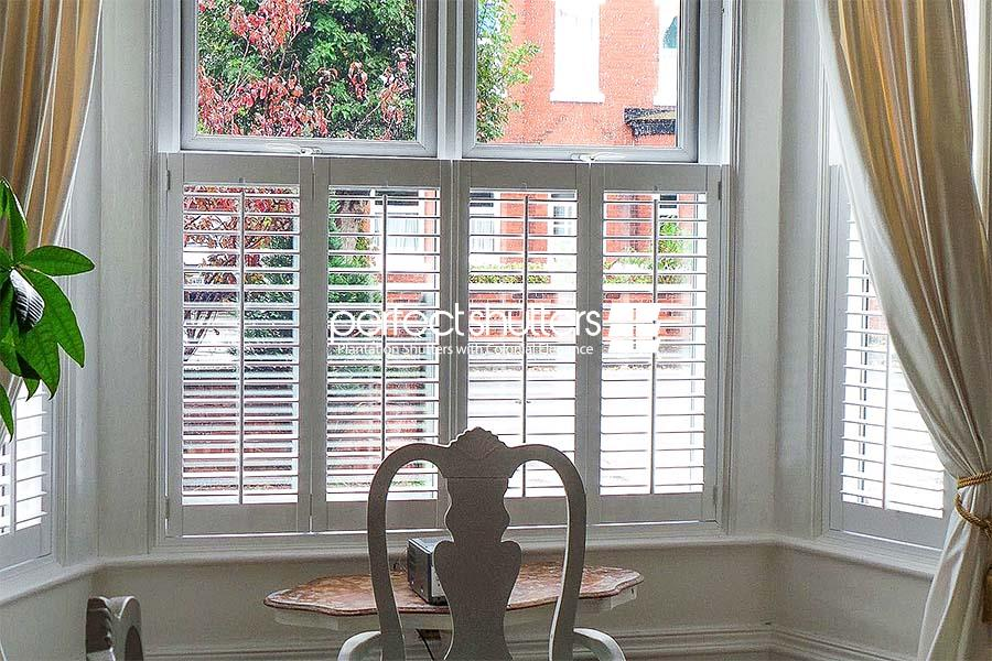Cafe style shutters with beige curtains