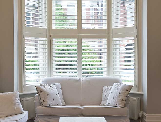 Bay Window Plantation Shutter in a living room, North West UK by Perfect Shutters